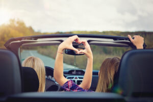 Two girls in convertable making heart with their hands